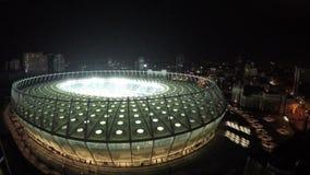 Arquitetura surpreendente da arena esportiva moderna iluminada na noite, tiro aéreo filme