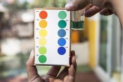 Arquivo da mão que guarda o teste dos testes do pH da água que compara a cor a dentro imagens de stock
