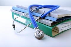 Arquivo do dobrador dos livros, estetoscópio, coração vermelho e prescrição de RX isolados no fundo branco Imagens de Stock