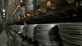 Arquivo do filme Os filmes, filme bobinam no shelfs em um arquivo velho enorme do filme vídeos de arquivo