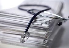 Arquivo e estetoscópio do dobrador dos livros isolados no fundo branco Imagem de Stock