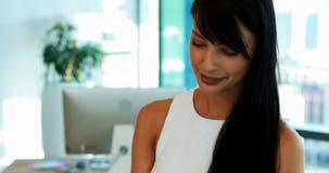 Arquivo executivo fêmea da leitura no escritório video estoque