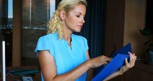 Arquivo executivo fêmea da leitura no escritório filme