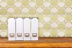 Arquivos brancos do compartimento em uma prateleira de madeira imagem de stock