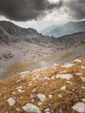 Arrástrese con paisaje de la alta montaña con las nubes y el sol de tormenta Fotografía de archivo