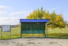 Arrêt d'autobus dans le village Le bouchon à côté de l'arbre photographie stock libre de droits