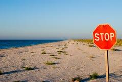Arrêt de panneau routier se tenant sur le soleil vide d'été de ciel bleu de mer de sable de plage Photos libres de droits