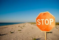 Arrêt de panneau routier se tenant sur le soleil vide d'été de ciel bleu de mer de sable de plage Photo libre de droits