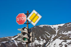 Arrêt ! Signes de route et feu de signalisation sur le ciel bleu Image stock