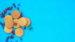 Arrêtez le fond de nourriture de mouvement Mini crêpes délicieuses de sourire avec des baies sur la surface bleue, vue supérieure banque de vidéos