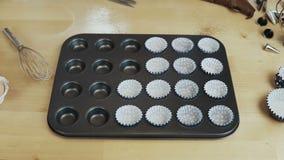 Arrêtez le mouvement Tasses de papier, emballages pour des petits gâteaux mettant dans le plateau de cuisson pour des petits pain clips vidéos