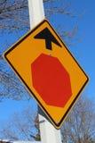 Arrêtez le signe en avant contre le ciel bleu et les arbres Image stock