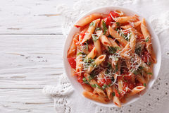 Arrabiata pasta penne with Parmesan cheese. Horizontal top view Royalty Free Stock Photo
