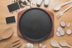 Arrabio que chisporrotea la placa del filete, utensilios rurales de la cocina en la tabla de madera Foto de archivo libre de regalías