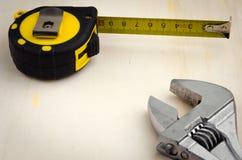 Arrachez et roulette de mesure sur un fond en bois Photographie stock