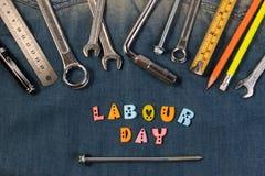 Arrachez les outils sur des travailleurs d'un denim avec l'espace pour le texte Jour de travail heureux Photographie stock