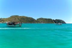 ARRAIAL ΚΑΝΕΤΕ CABO, ΡΊΟ ΝΤΕ ΤΖΑΝΈΙΡΟ, ΒΡΑΖΙΛΊΑ 21 ΜΑΡΤΊΟΥ 2016: Μια βάρκα πέρα από πράσινα και σαφή νερά κοντά σε μια ακτή Στοκ εικόνα με δικαίωμα ελεύθερης χρήσης