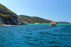 ARRAIAL ΚΑΝΕΤΕ CABO, ΡΊΟ ΝΤΕ ΤΖΑΝΈΙΡΟ, ΒΡΑΖΙΛΊΑ 21 ΜΑΡΤΊΟΥ 2016: Sailboat και μια βάρκα πέρα από πράσινα και σαφή νερά κοντά σε μ Στοκ φωτογραφία με δικαίωμα ελεύθερης χρήσης