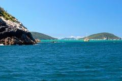 ARRAIAL ΚΑΝΕΤΕ CABO, ΡΊΟ ΝΤΕ ΤΖΑΝΈΙΡΟ, ΒΡΑΖΙΛΊΑ 21 ΜΑΡΤΊΟΥ 2016: Sailboat και μια βάρκα πέρα από πράσινα και σαφή νερά κοντά σε μ Στοκ Φωτογραφία