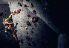 Arrampicarsi di pratica d'uso degli abiti sportivi della giovane donna su una parete all'interno immagini stock