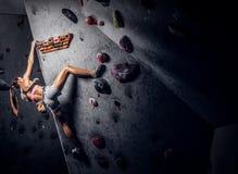 Arrampicarsi di pratica d'uso degli abiti sportivi della giovane donna su una parete all'interno fotografia stock