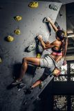 Arrampicarsi di pratica d'uso degli abiti sportivi della giovane donna su una parete all'interno fotografie stock