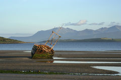 Arran boat. A derelict fishing boat at Ettrick Bay, Bute, with the island of Arran in the background royalty free stock photography