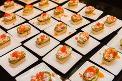 Arrancadores gastrónomos deliciosos del canapé en las placas blancas Foto de archivo libre de regalías