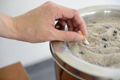 Arrancando para fora o cigarro no escaninho do cinzeiro da areia Fotografia de Stock Royalty Free