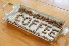 Arrange coffee beans to make the word coffee. In a stainless tray on a wooden table Stock Images