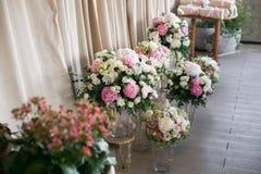 Arrange flowers in a white roman vase.  Stock Image