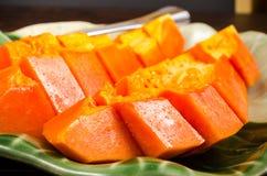 Arrange fresh yellow papaya on green leaf dish. Arrange fresh papaya on green leaf dish on wooden background Royalty Free Stock Photo