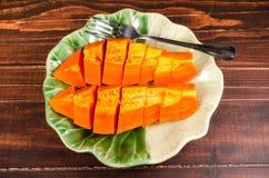 Arrange fresh yellow papaya on green leaf dish. Arrange fresh papaya on green leaf dish on wooden background Stock Photography