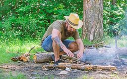 Arrange the woods twigs or wood sticks standing like a pyramid and place the leaves under. How to build bonfire outdoors. Man straw hat prepares bonfire in stock images