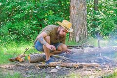 Arrange the woods twigs or wood sticks standing like a pyramid and place the leaves under. Ultimate guide to bonfires. How to build bonfire outdoors. Man straw royalty free stock image