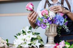 Arrangeant les fleurs artificielles investissent la d?coration ? la maison, travail de fleuriste de jeune femme faisant la fleur  image stock