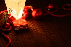 Arranged Christmas adornments and small present box in light of lantern. Stock Photography