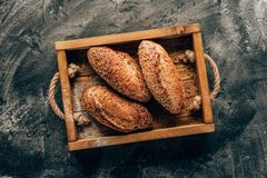 Arranged loafs of bread in wooden box on dark tabletop with flour. Top view of arranged loafs of bread in wooden box on dark tabletop with flour Royalty Free Stock Photography