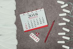 Arranged menstrual pads and tampons, calendar and pills on grey surface. Top view of arranged menstrual pads and tampons, calendar and pills on grey surface royalty free stock photography