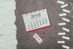 Arranged menstrual pads and tampons, calendar and pills on grey surface. Top view of arranged menstrual pads and tampons, calendar and pills on grey surface stock image