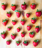 Arranged pattern of strawberries on a wooden board. Arranged strawberries on a wooden board Royalty Free Stock Image