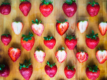 Arranged pattern of strawberries on a wooden board. Arranged fresh strawberries on a wooden board Royalty Free Stock Image