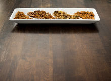 Arranged Pecans, Walnuts, and Almonds on White Tray, copy space. Royalty Free Stock Image
