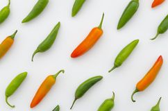 Arranged red, yellow, and green peppers on white background. Vegetables in diagonal direction composition. Flat lay top. Red, yellow, and green peppers on white royalty free stock photo