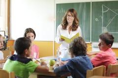 Arrangement élémentaire de salle de classe. Foyer sur le professeur et le tableau. Image libre de droits