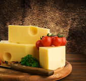 Arrangement with appetizing cheese on the kitchen cutting board Royalty Free Stock Images