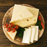 Arrangement with appetizing cheese on the kitchen cutting board Stock Images