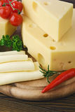 Arrangement with appetizing cheese on the kitchen cutting board Royalty Free Stock Photos