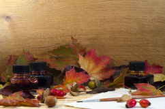 Arrangement of autumn leaves, nuts and berries and painting equi Stock Image