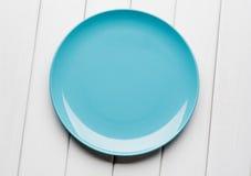Arrangement blanc de table d'en haut Plat bleu vide sur le bois planked photographie stock libre de droits